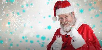 Zusammengesetztes Bild von nettem Weihnachtsmann Glas des Milch- und Sternformplätzchens zeigend Lizenzfreies Stockbild