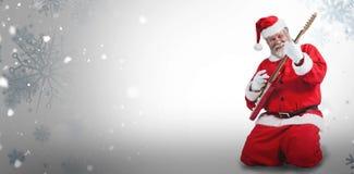 Zusammengesetztes Bild von nettem Weihnachtsmann kniend und Gitarre spielend Stockfoto