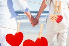 Zusammengesetztes Bild von Paaren auf dem Strand, der heraus zum Seehändchenhalten schaut Lizenzfreies Stockbild