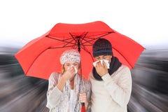 Zusammengesetztes Bild von Paaren im Winter arbeiten das Niesen unter Regenschirm um Stockfoto