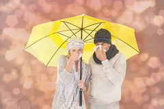 Zusammengesetztes Bild von Paaren im Winter arbeiten das Niesen unter Regenschirm um Stockfotografie