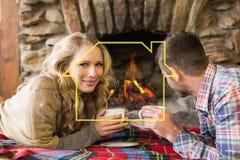 Zusammengesetztes Bild von Paaren mit Teeschalen vor beleuchtetem Kamin Lizenzfreies Stockfoto