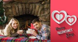 Zusammengesetztes Bild von Paaren mit Teeschalen vor beleuchtetem Kamin Stockfoto