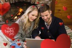 Zusammengesetztes Bild von Paaren unter Verwendung des Laptops vor beleuchtetem Kamin Stockfotografie