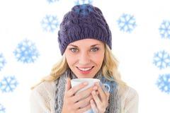 Zusammengesetztes Bild von recht blondem auf die Wintermode, die Becher hält Lizenzfreies Stockfoto