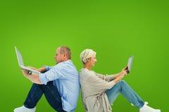 Zusammengesetztes Bild von reifen Paaren unter Verwendung des Laptop- und Tabletten-PC Lizenzfreie Stockfotografie