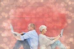 Zusammengesetztes Bild von reifen Paaren unter Verwendung des Laptop- und Tabletten-PC Stockfoto