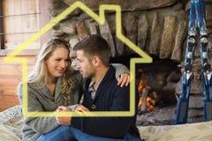 Zusammengesetztes Bild von romantischen Paaren vor beleuchtetem Kamin Stockfotografie