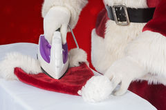 Zusammengesetztes Bild von Vaterweihnachten bügelt seinen Hut Lizenzfreies Stockfoto