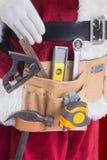 Zusammengesetztes Bild von Vaterweihnachten trägt einen Werkzeuggurt Lizenzfreies Stockfoto