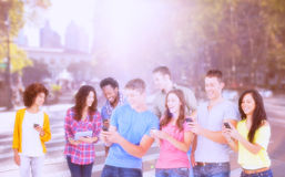 Zusammengesetztes Bild von vier lachenden Freunden, die Texte an ihren Telefonen senden Lizenzfreie Stockfotos