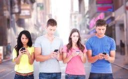 Zusammengesetztes Bild von vier Leuten, die neben einander stehen und an ihren Telefonen simsen Lizenzfreies Stockbild
