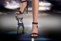 Zusammengesetztes Bild von weiblichen Füßen in den schwarzen Sandalen, die auf Geschäftsmann treten Lizenzfreie Stockfotografie