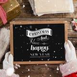 Zusammengesetztes Bild von Weihnachtsmann einen Schiefer mit Text der frohen Weihnachten halten Stockfotos