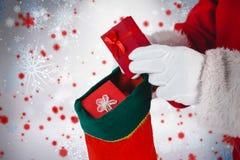 Zusammengesetztes Bild von Weihnachtsmann Geschenke in Weihnachtsstrümpfe einsetzend Lizenzfreie Stockbilder