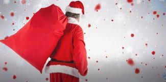 Zusammengesetztes Bild von Weihnachtsmann rote Tasche von Geschenken voll tragend Stockfoto