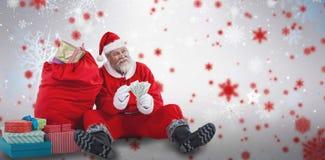 Zusammengesetztes Bild von Weihnachtsmann sitzend durch die Weihnachtsgeschenke, die Rechnungen zählen Lizenzfreie Stockbilder