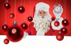 Zusammengesetztes Bild von Weihnachtsmann Wecker und Zeichen halten Lizenzfreie Stockfotografie