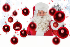 Zusammengesetztes Bild von Weihnachtsmann Wecker und Zeichen halten Stockfoto