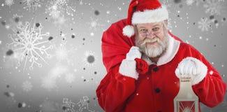 Zusammengesetztes Bild von Weihnachtsmann Weihnachtstasche und -laterne halten Stockfotografie