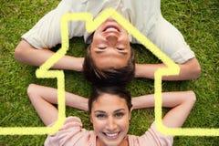 Zusammengesetztes Bild von zwei Freunden, die beim Lügen Kopf-an-Kopf- mit beiden Händen hinter ihrem Hals lächeln Lizenzfreies Stockbild