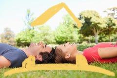 Zusammengesetztes Bild von zwei lächelnden Freunden, die beim Lügen Kopf-an-Kopf- aufwärts schauen Stockfoto