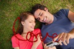 Zusammengesetztes Bild von zwei lächelnden Freunden, die Fotos auf einer Kamera betrachten Lizenzfreies Stockbild
