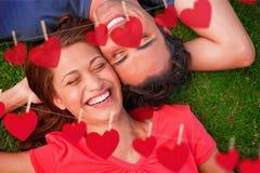 Zusammengesetztes Bild von zwei lächelnden Freunden während Lügenkopf zur Schulter mit einem Arm hinter ihrem Kopf Stockbild