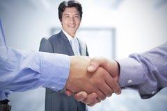 Zusammengesetztes Bild von zwei Männern, die Hände rütteln Lizenzfreies Stockbild