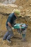 Zusammenpressender Sand der Arbeitskraft mit Vibrationsplattebesetzer Stockfotos