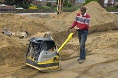 Zusammenpressender Sand der Arbeitskraft mit Vibrationsplattebesetzer Lizenzfreie Stockbilder