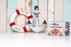 Zusammensetzung auf einem Marinethema mit einem Anker und eine Lebenboje, Muscheln und Starfish auf einem hölzernen Hintergrund lizenzfreies stockbild