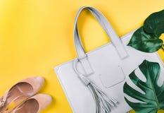 Zusammensetzung der weiblichen Handtasche, der Schuhe und des grünen Blattes stockfotografie