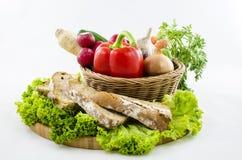 Zusammensetzung des Brotes und des Gemüses auf hölzernem Brett Lizenzfreie Stockbilder