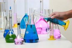 Zusammensetzung des Labormaterials mit farbigen Flüssigkeiten im reali Stockfotos