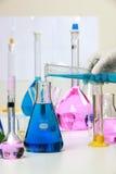 Zusammensetzung des Labormaterials mit farbigen Flüssigkeiten im reali Lizenzfreie Stockfotografie