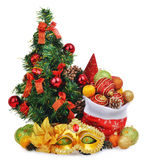 Zusammensetzung des neuen Jahres mit Weihnachtsbaum, Weihnachtsmann-Tasche voll von Spielwaren und Karnevalsmaske Stockfotografie