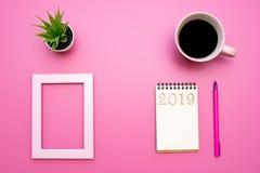 Zusammensetzung 2019 des Notizblockes, des Stiftes, der Kaffeetasse mit Blume und des Fotorahmens stockfoto