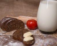Zusammensetzung des Schwarzbrots der Tomate und der Milch Stockfotos