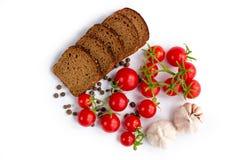 Zusammensetzung des Schwarzbrots, der Tomaten und des Knoblauchs Stockfotos