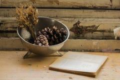 Zusammensetzung einer Metallplatte gefüllt mit Kiefernkegeln, verwelkten Blumen und einem Buch Lizenzfreies Stockfoto