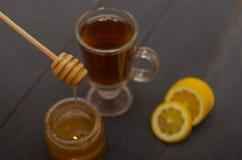 Zusammensetzung einer Tasse Tee, geschnittene Zitrone und ein Glas Honig stockbilder