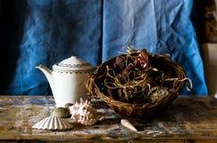 Zusammensetzung einer Teekanne, Korb voll von verwelkten Blumen und Muscheln Stockbilder