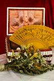 Zusammensetzung eines Kastens, der verwelkten Blumen und des Handfans Lizenzfreies Stockfoto