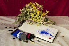 Zusammensetzung eines Sketchbook, der verwelkten Blumen, der Knöpfe und der Farbe Lizenzfreie Stockfotos