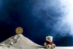 Zusammensetzung eines Spielzeugs und der Uhr auf dem Sand Stockbilder