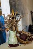 Zusammensetzung eines Vase, der verwelkten Blumen, des Granatapfels in einem Korb und des Mais Stockbilder