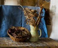 Zusammensetzung eines Vase, des Korbes und der verwelkten Blumen Stockfotografie