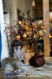 Zusammensetzung eines Vase füllte mit verwelkten Blumen, Granatapfel und einem Glas Stockbilder