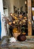 Zusammensetzung eines Vase füllte mit verwelkten Blumen, rapana und einem Granatapfel Stockfotos